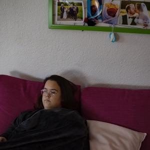 Ich liege auf meiner Couch, zugedeckt. Im Hintergrund Hochzeitsbilder und Luis und Robin